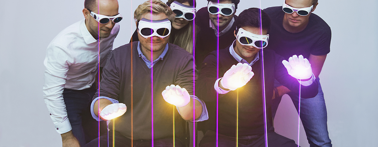 Six people wearing protective goggles looking at lasers